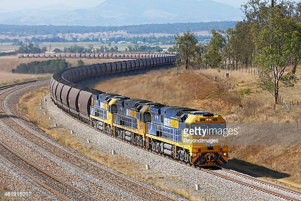 Heavy Pacific National loaded coal train winds slowly uphill
