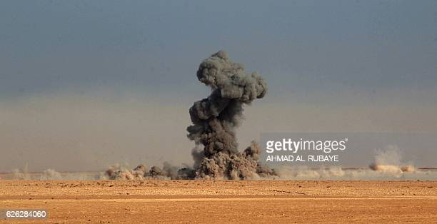 A heavy plume of smoke if seen as Iraqi Shiite fighters from the Hashed alShaabi paramilitaries advance in a desert area near the village of Tall...