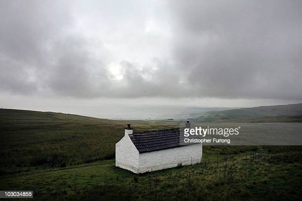 Heavy rain clouds loom over a holiday cottage in the North Pennines on July 22 2010 Near Alston England Much of the United Kingdom is experiencing...