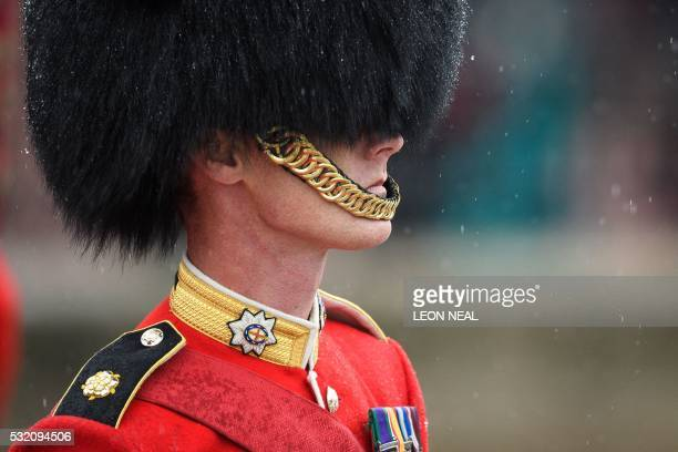 Heavy rain hits the Mall as a soldier from The Coldstream Guards waits for Britain's Queen Elizabeth II to return to Buckingham Palace from the...