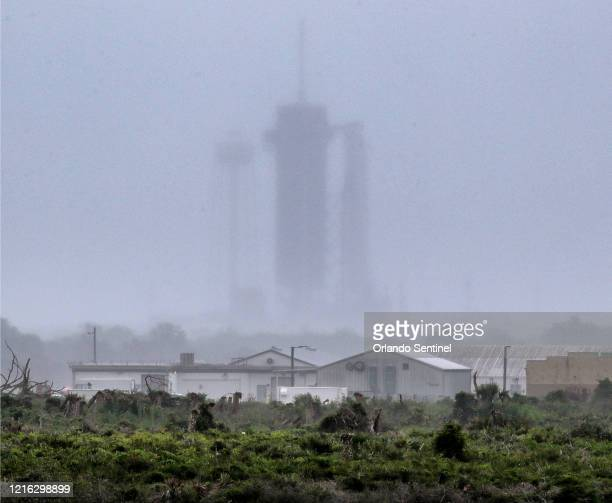 Heavy rain moves over Launch Complex 39-A at Kennedy Space Center, Fla., two hours before the scheduled launch of a SpaceX Falcon 9 rocket carrying...