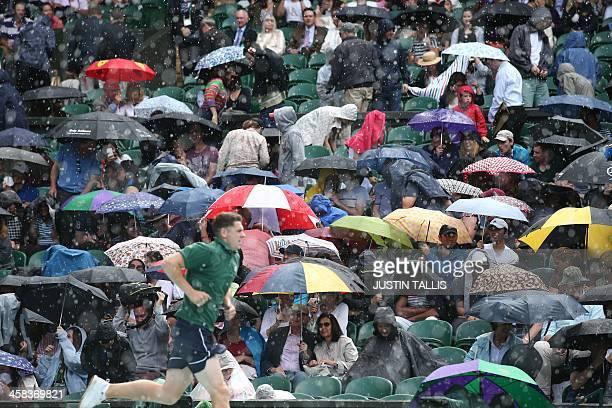 TOPSHOT A heavy rain shower falls on the spectators on centre court interrupting the men's singles third round match between Australia's John Millman...