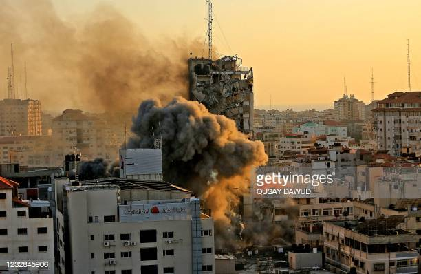 Heavy smoke and fire rise from Al-Sharouk tower as it collapses after being hit by an Israeli air strike, in Gaza City, on May 12, 2021. - An Israeli...