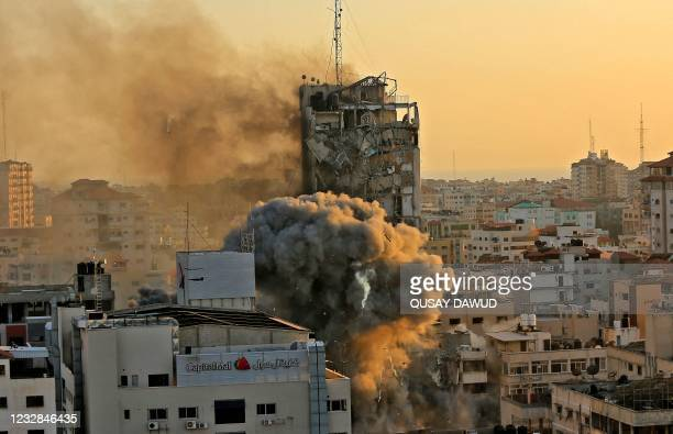 Heavy smoke and fire rise from Al-Sharouk tower as it collapses after being hit by an Israeli air strike, in Gaza City on May 12, 2021. - An Israeli...