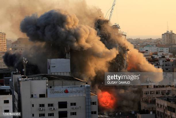 Heavy smoke and fire surround Al-Sharouk tower as it collapses during an Israeli air strike, in Gaza City on May 12, 2021. - An Israeli air strike...