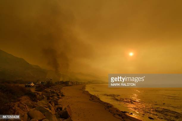 Heavy smoke covers the seaside enclave of Mondos Beach beside the 101 highway as flames reach the coast during the Thomas wildfire near Ventura...