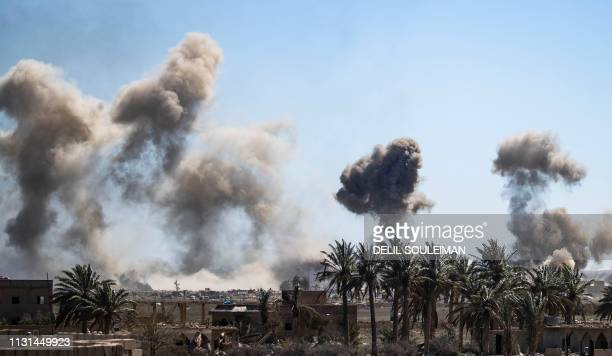 Heavy smoke rises above the Islamic State group's last remaining position in the village of Baghouz during battles with the Syrian Democratic Forces...