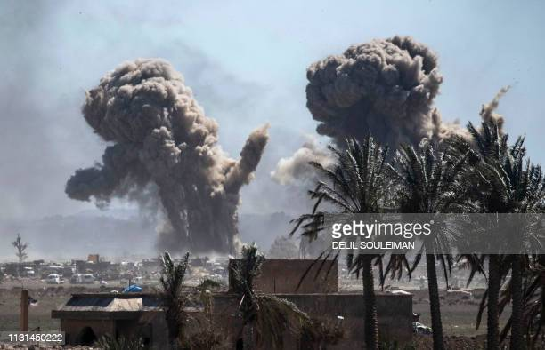 TOPSHOT Heavy smoke rises above the Islamic State group's last remaining position in the village of Baghouz during battles with the Syrian Democratic...
