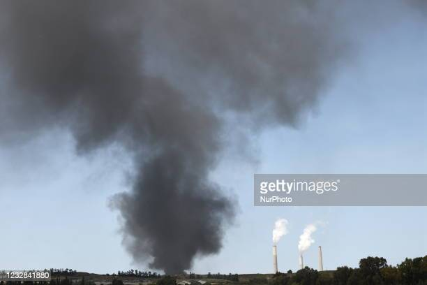 Heavy smoke rises from a large tank belonging to the Eilat-Ashkelon oil pipeline, after being hit by a rocket on May 12 near Ashkelon.