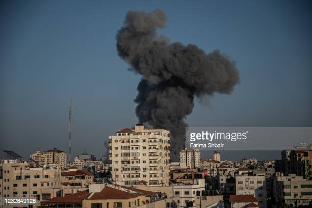 Heavy smoke surround Al-Sharouk tower as it collapses during an Israeli air strike, in Gaza City on May 12, 2021 in Gaza City, Gaza. At least three...