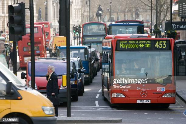 Heavy traffic at a standstill at traffic lights in Trafalgar Square London city centre England United Kingdom