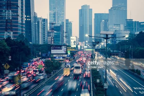 heavy traffic captured with blurred motion along the gatot subroto highway in the heart of jakarta business district in indonesia - emerging markets stock photos and pictures