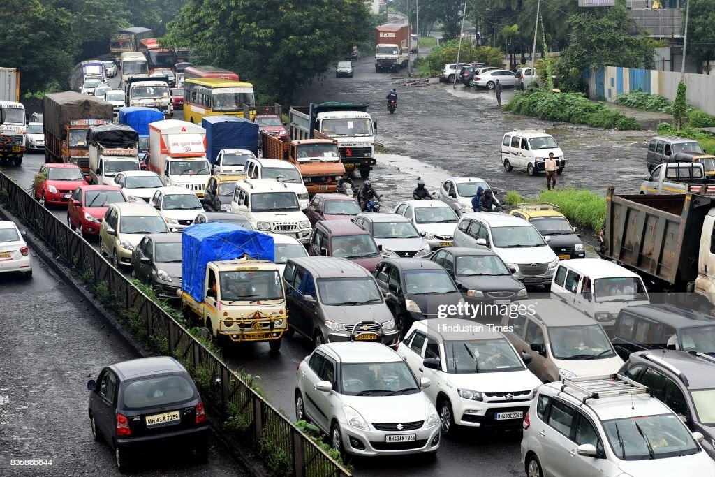 Heavy traffic jam due to bad condition of roads at Sion Panvel near Turbhe during the rain, on August 19, 2017 in Mumbai, India. These weather conditions have been attributed to the presence of a low pressure which is currently lying over the Vidarbha region. Due to this, moisture incursion has increased over Mumbai as well as Thane and the cities have recorded these heavy spells.