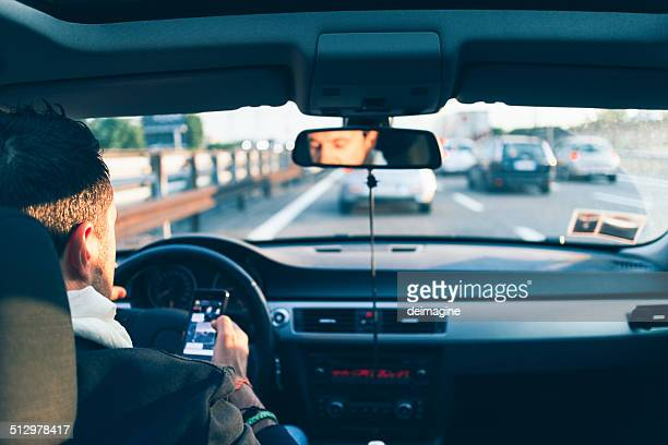 Heavy traffic, man checks smartphone