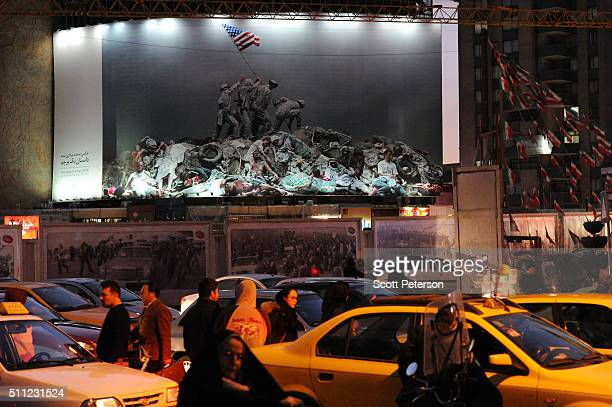 Heavy traffic moves around Tehran's central Vali Asr Square beneath a large antiAmerican banner that depicts US Marines raising the flag at Iwo Jima...
