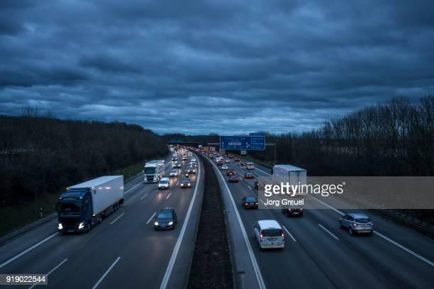 heavy traffic on autobahn (dusk) - verkehrswesen stock-fotos und bilder