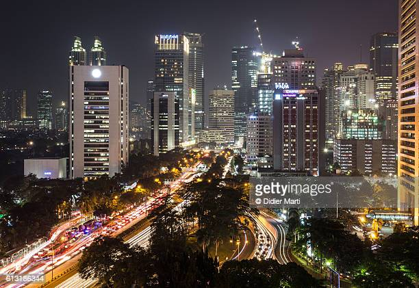 heavy traffic on jalan sudirman in jakarta at night - emerging markets stock photos and pictures