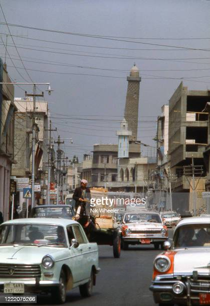 Heavy traffic on street in downtown Mosul, largest city in Northern Iraq, with Leaning Minaret of the Great Mosque in the background, circa 1978