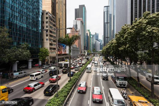 heavy traffic on the road between the wan chai and causweay bay district in hong kong - wanchai stock photos and pictures