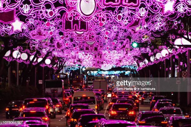 Heavy traffic under illuminated arch on Orchard street in Singapore