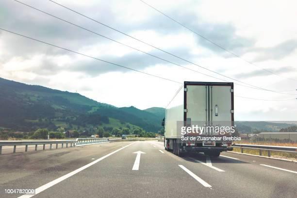 heavy transport. truck traveling on a quiet main road surrounded by nature - motorista ocupação imagens e fotografias de stock