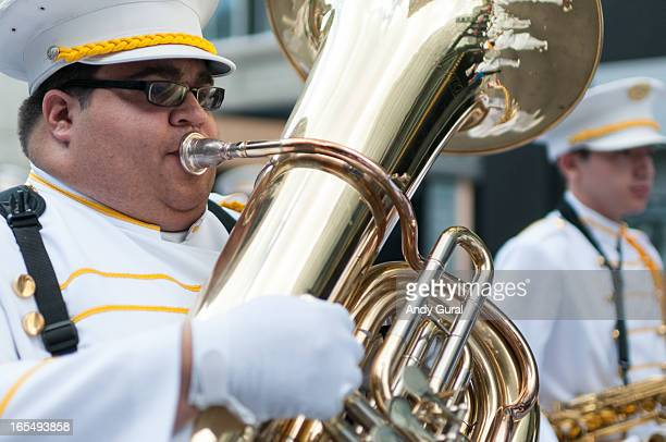 CONTENT] A heavyset gentleman in a white uniform with gold braid plays the tuba in a parade