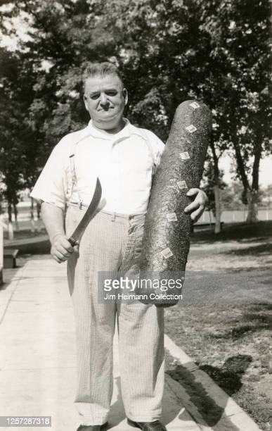A heavyset man in seersucker pants a white shirt and suspenders holds a giant sausage in one hand and knife in the other circa 1934