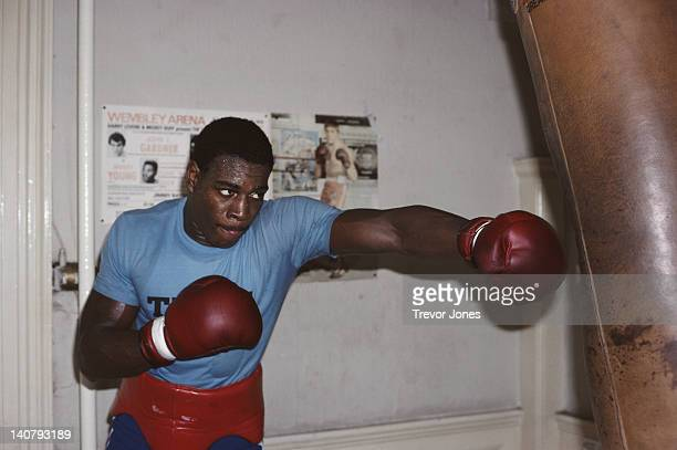 Heavyweight boxer Frank Bruno hitting the punch bag during training on 1st September 1983 at the Royal Oak gym in Canning Town London Great Britain