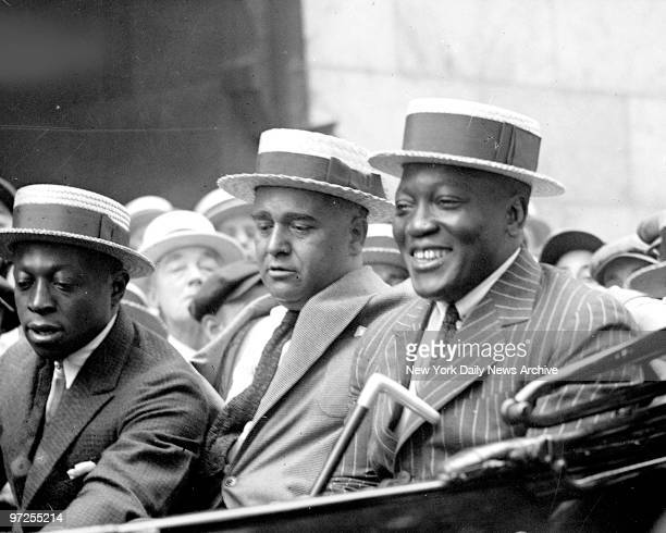Heavyweight boxer Jack Johnson rides through crowd in Harlem