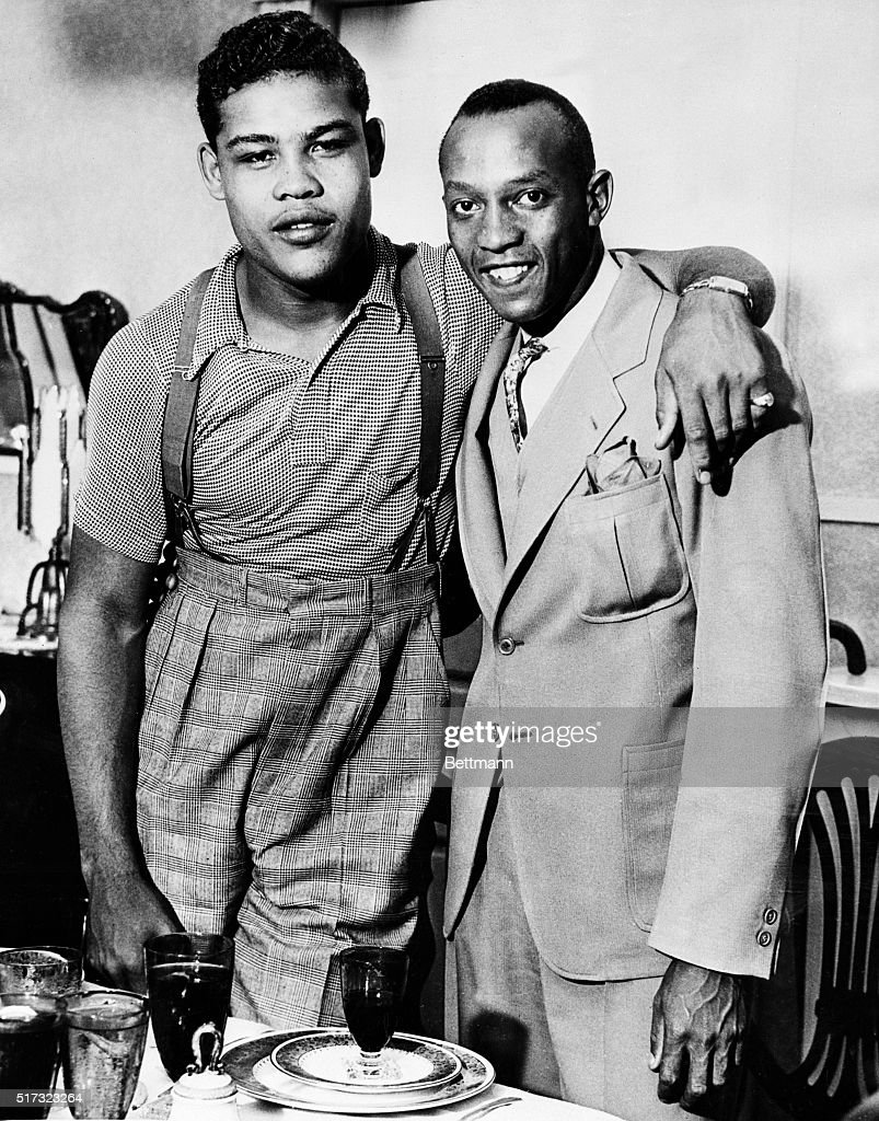 Heavyweight boxer Joe Louis puts his arm around Jesse Owens, Ohio State University track star and holder of three world's records. They were introduced during a boxing program sponsored by the Colored Elks. Washington, D.C., August 27, 1935.