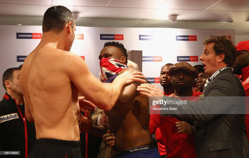 Heavyweight boxer Vitali Klitschko of Ukraine (L) reacts after he received a slap in the face by Dereck Chisora (C) of the UK during the weigh in for their upcoming WBC heavyweight title fight at Karstadt Sports shopping center on February 17, 2012 in Munich, Germany.
