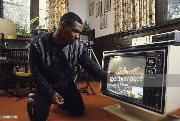 Casual portrait of Mike Tyson watching video of fight at the home of his surrogate mother Camille Ewald. Catskill, NY 12/1/1985 CREDIT: Manny Millan
