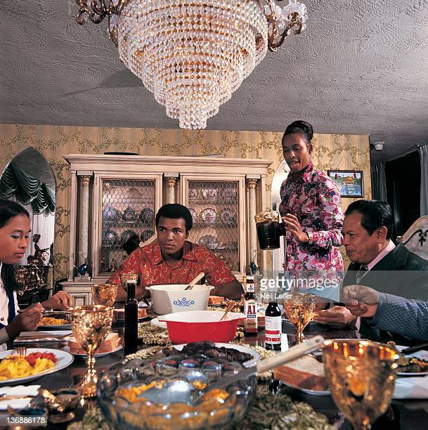 Heavyweight Boxing Casual portrait of Muhammad Ali and wife Khalilah entertaining Indonesian fight promoters during photo shoot in the dining room of...