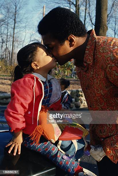 Heavyweight Boxing Casual portrait of Muhammad Ali kissing his daughter Jamillah outside of home during photo shoot on Barbara Drive in Voken Tract...
