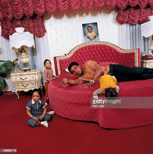 Heavyweight Boxing Casual portrait of Muhammad Ali with children twin daughters Jamillah and Rasheda and son Ibn Muhammad Ali Jr in bedroom during...