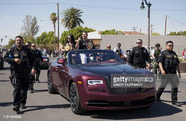 Heavyweight boxing champion Andy Ruiz Jr and his wife Julie wave to supporters during a parade in his honour on June 22 2019 in Imperial California...