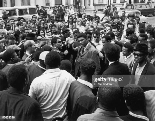 Heavyweight boxing champion Cassius Clay surrounded by fans and photographers during a visit to the London Free School children's play group and...