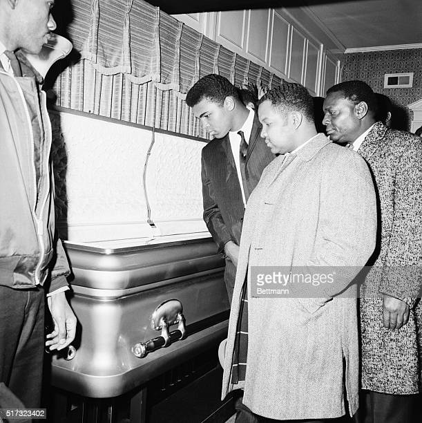 Heavyweight boxing champion Cassius Clay views the body of soul singer Sam Cooke at his wake in Chicago