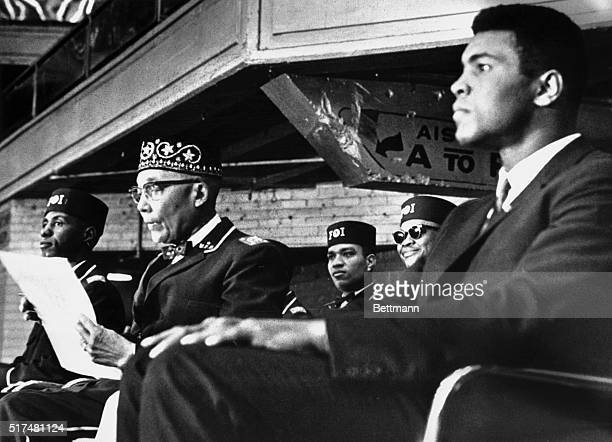 Heavyweight boxing champion Muhammad Ali sits on the podium with Nation of Islam leader Elijah Muhammad while attending the National Meeting of the...