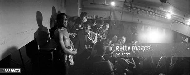 Heavyweight Boxing Panoramic view of Muhammad Ali during media interview with press in locker room after winning fight vs Doug Jones at Madison...