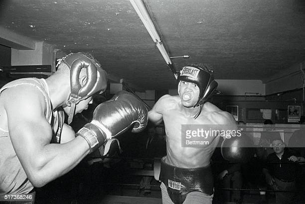 Heavyweight Cassius Clay flexes muscles and grimaces as he smashes sparring partner Cody Jones knocking him through the ropes