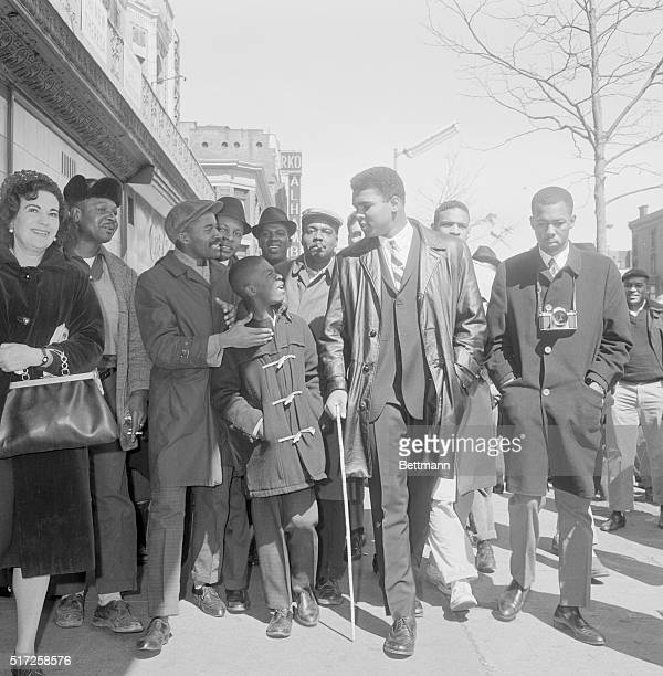 Heavyweight champion Cassius Clay has a flock of young admirers as he walks along the streets of New York. The new champ refused to talk about his...