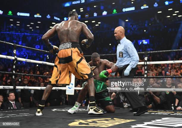 Heavyweight champion Deontay Wilder of the US knocks down contender Luis Ortiz of Cuba during their WBC heavyweight title bout in New York on March 3...