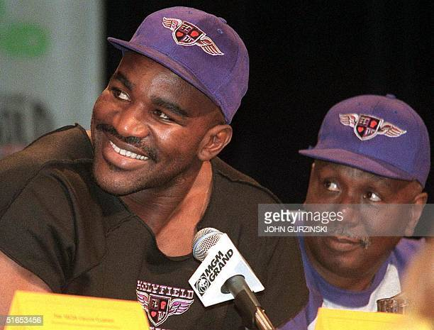 Heavyweight champion Evander Holyfield sits with trainer Don Turner during a 25 June press conference at the MGM Grand Hotel in Las Vegas, NV....