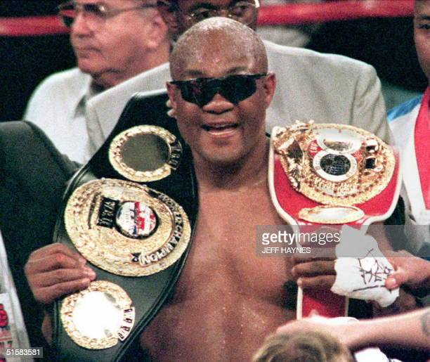 Heavyweight champion George Foreman of the US smiles as he holds belts for the International Boxing Federation championship and the World Boxing...