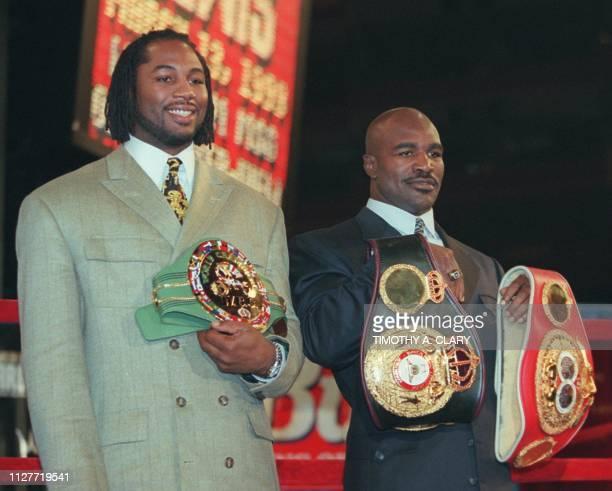 WBC heavyweight champion Lennox Lewis of Great Britain and WBA heavyweight champ Evander Holyfield of the US pose for pictures with their...