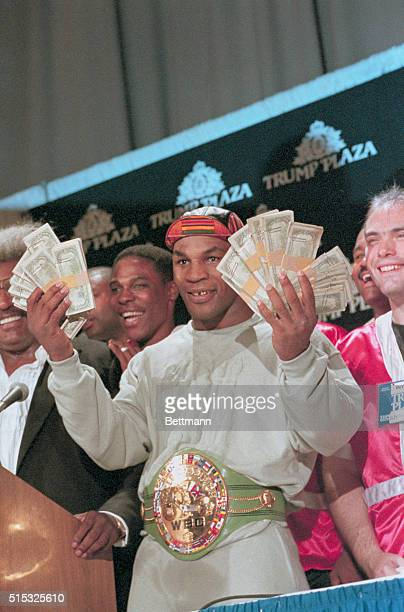 Heavyweight champion Mike Tyson flashes the $100000 bonus given him by promoter Don King for knocking out Carl Williams in the first round of their...