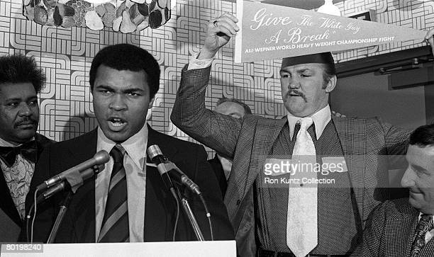 "Heavyweight champion Muhammad Ali addresses the media while challenger Chuck Wepner holds up a pennant the reads, ""Give the White Guy a Break"" during..."