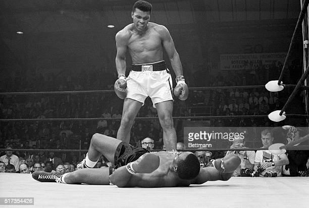 Heavyweight champion Muhammad Ali stands over Sonny Liston and taunts him to get up during their title fight. Ali knocked Liston out in one minute in...