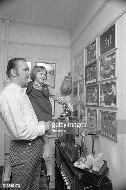 Heavyweight Chuck Wepner shows him daughter, Kim 3, trophies, photographs and other mementoes of his ring career as they relax at their Bay Bayonne...